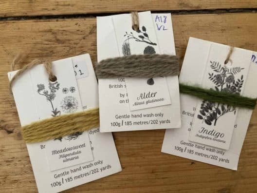 Three yarn labels from with yarn wrapped around each, displaying the colour and the name of the dyestuff used