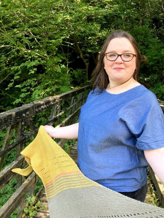 Louise is standing on a footbridge in a wood. She is wearing a blue handmade top and she holds a triangular shape garter stitch shawl