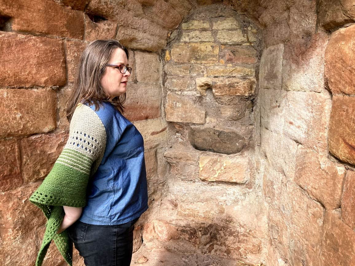 Louise stands in an alcove of pinkish stone. She stands with her right side toward the camera. She is wearing her gryer shawl around her shoulders.